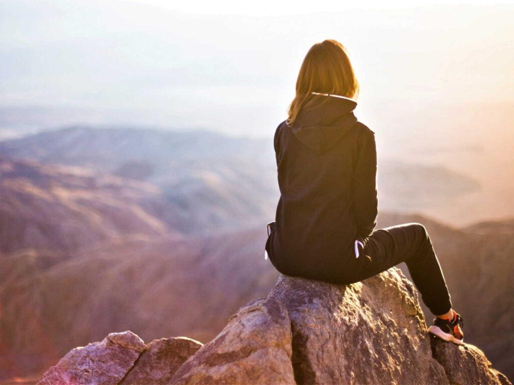 Frau auf einem Felsen als Symbol für Marketing Kommunikations Trends